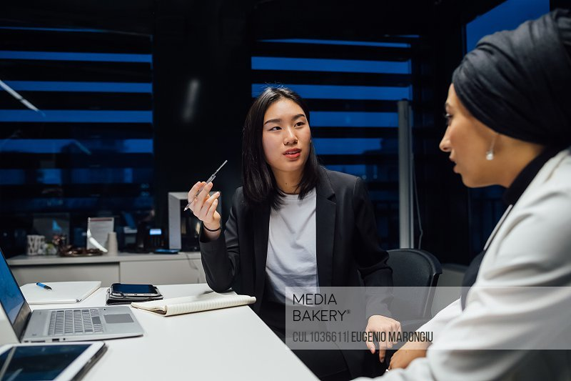 Businesswomen having discussion during conference table meeting