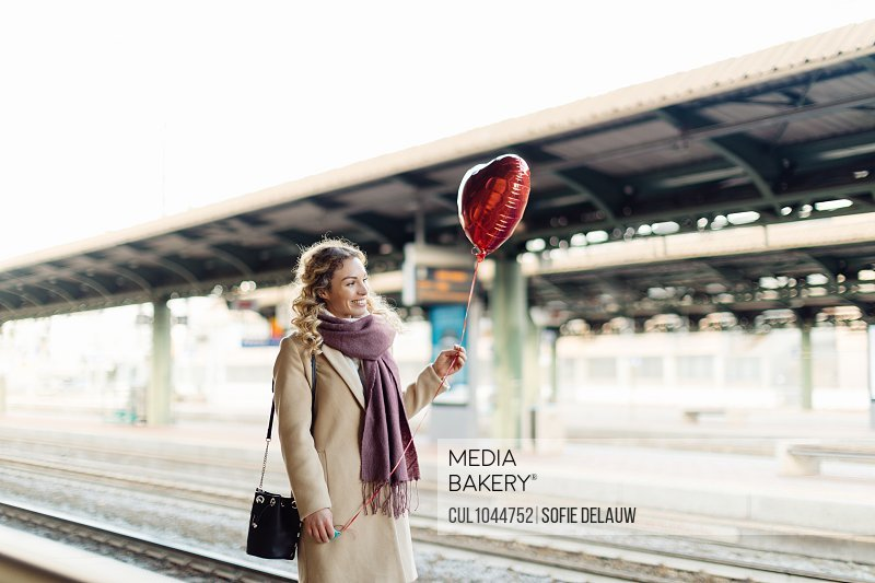 Woman with heart shaped balloon at train station, Firenze, Toscana, Italy
