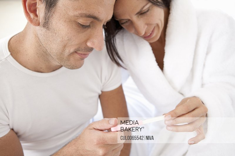 Couple reading pregnancy test together