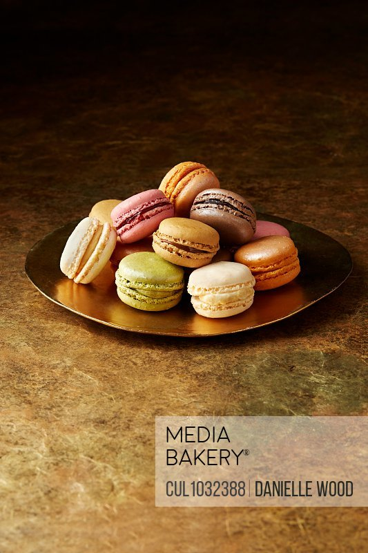 Still life with flavoured macaroons on gold plate
