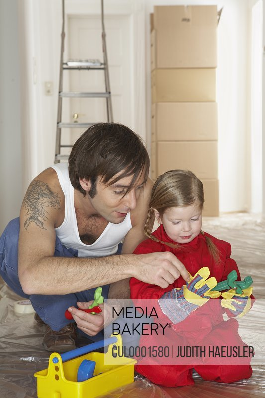 Girl (3-5) with father playing with plastic toolset