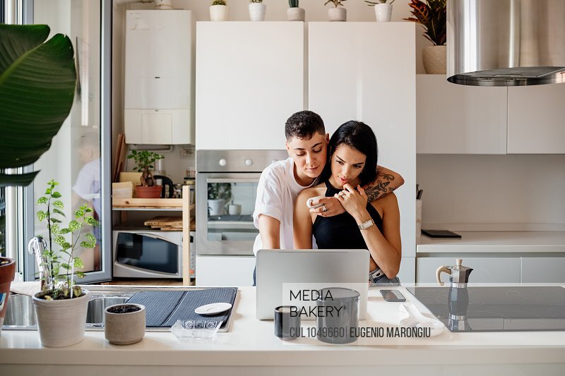 Young lesbian couple standing in kitchen, using laptop.