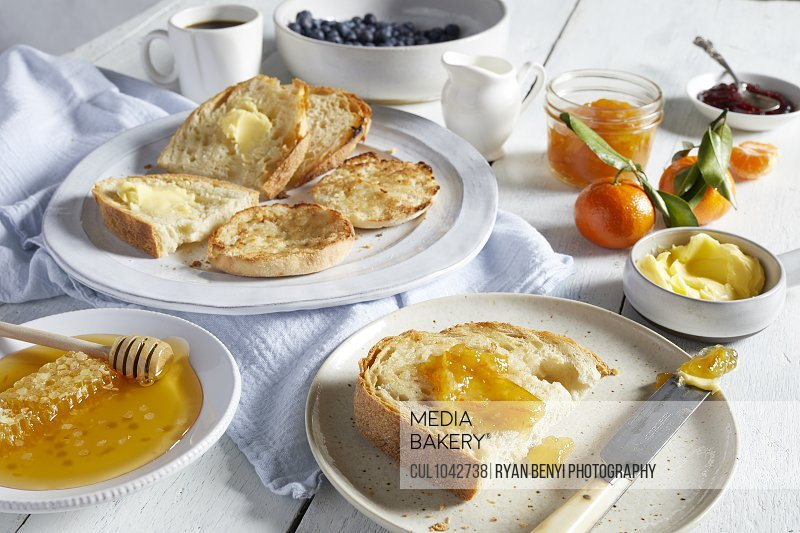 Plates of toast with butter and marmalade, dishes of honey, butter and jams.