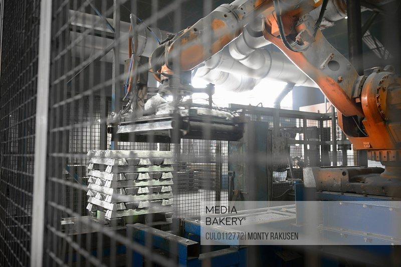 Heavy machinery lifting metal ingots at aluminum recycling plant