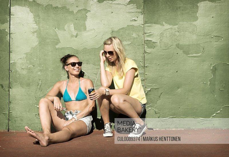 Teenage girls sharing headphones