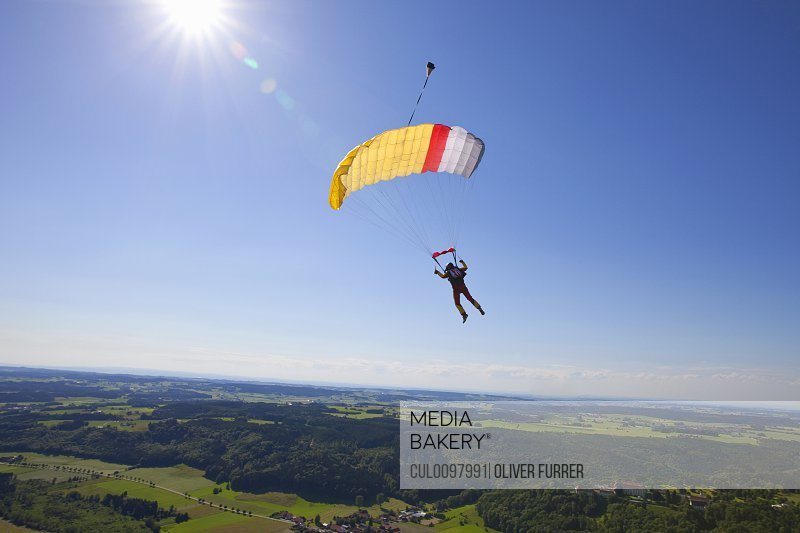 Man parachuting over rural landscape