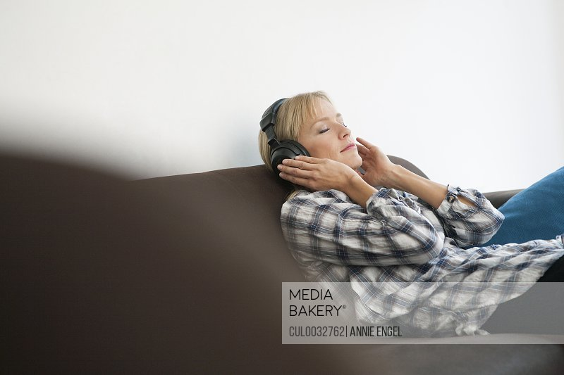 woman on couch with headphones