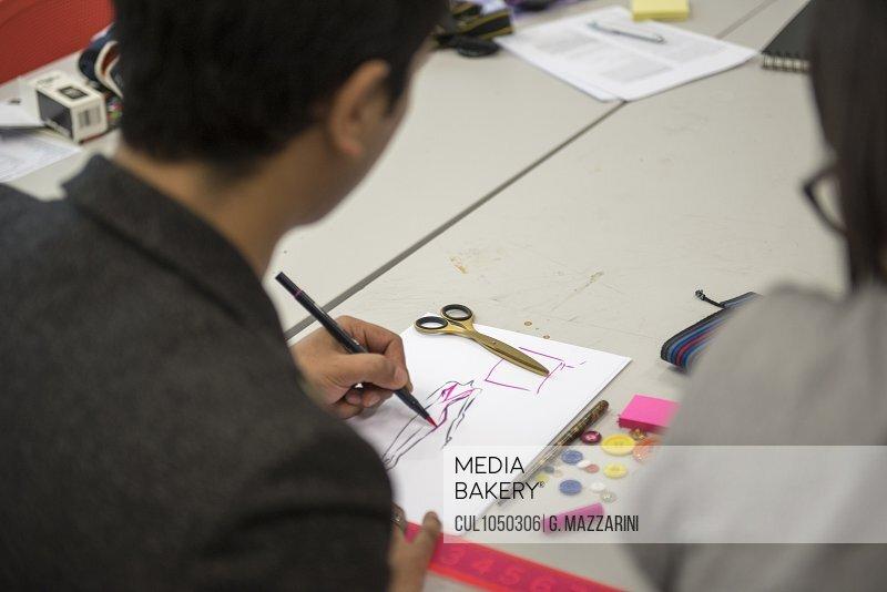 Fashion student sketching design