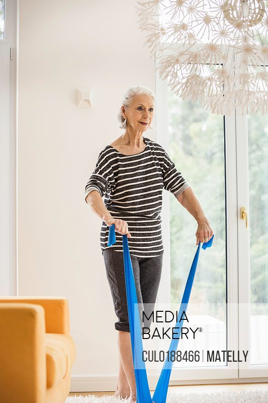 Senior woman exercising in living room pulling resistance band