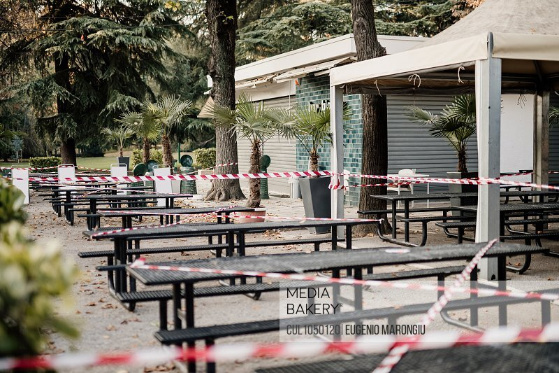 Cordon tape around seating outside cafe during 2020 Covid-19 Lockdown, Milan, Italy