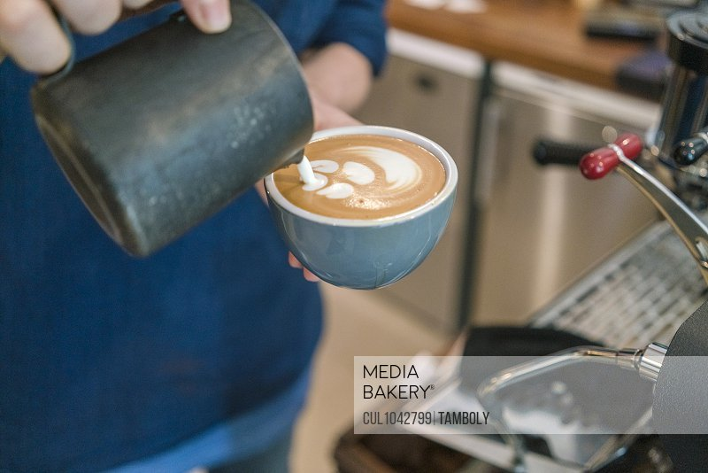 Close up of a jug of milk being poured into a cup of coffee by a barista.