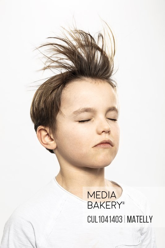 Boy with flying hair closing eyes, white background