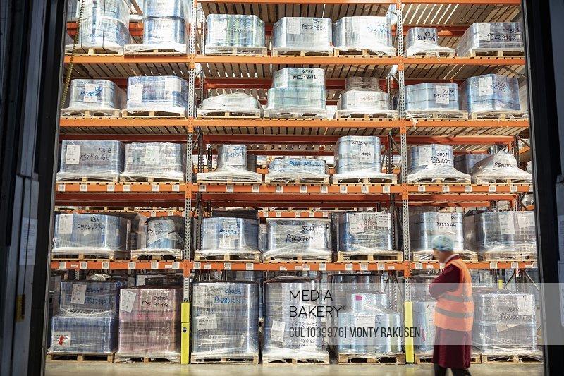 Printed food packaging in storage in print factory and worker