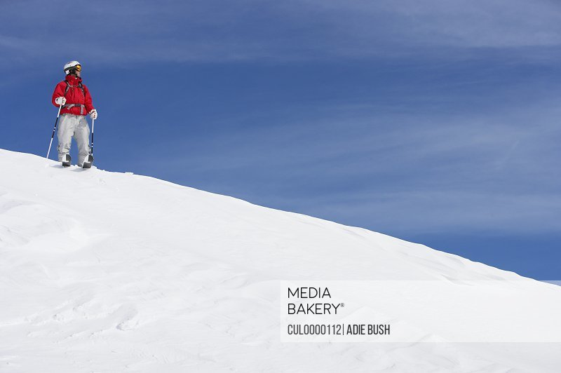 Male skier standing on snow covered slope