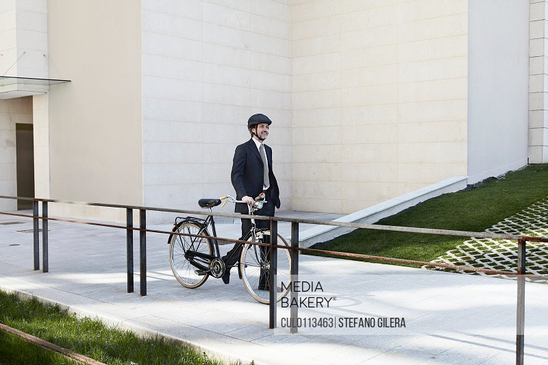 Mid adult businessman walking with bicycle