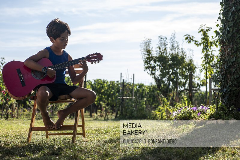 A boy sitting on a chair in the garden playing a guitar.