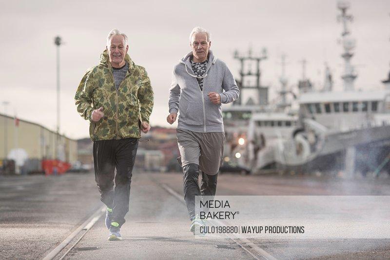 Front view of men jogging on docklands
