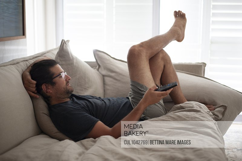 A man lounging on a sofa wearing shorts and a t shirt holding a remote control, staying at home.