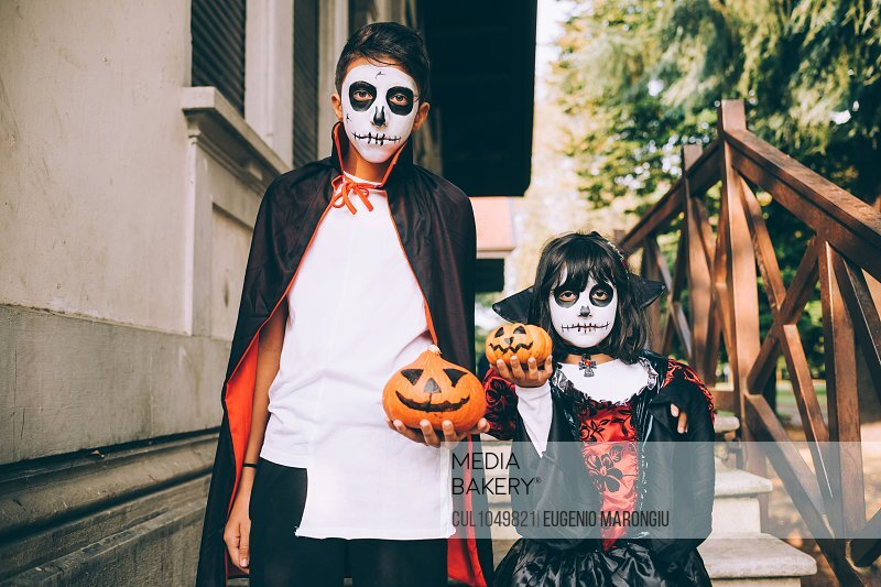 Brother and sister in Halloween costumes with Jack-O-Lanterns