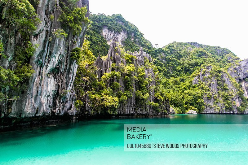 Secluded lagoon surrounded by beaches and high limestone cliffs near El Nido, Palawan, Philippines