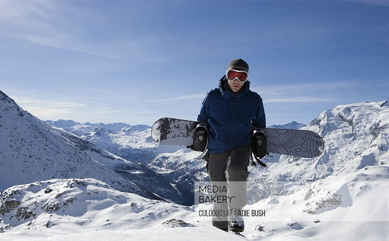 Male snowboarder walking up mountain ridge carrying snowboard