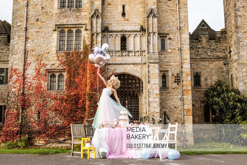 Bride standing on table outside castle holding balloons