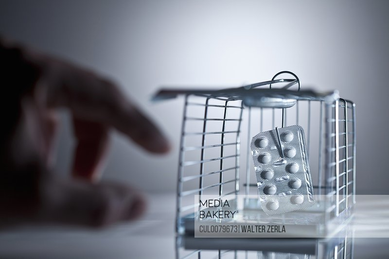 Blister pack of pills in cage trap