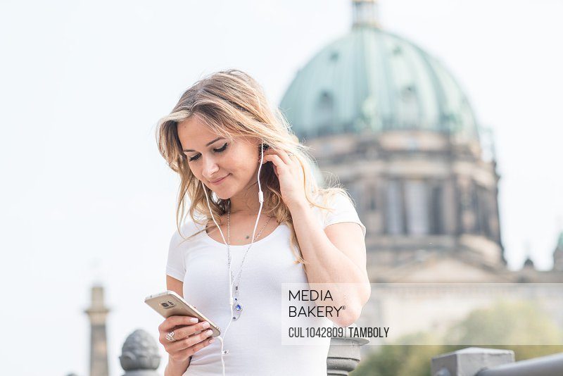 Smiling blond woman using smartphone with headphones standing near Berlin Cathedral, Germany.