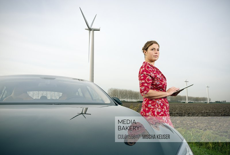 Woman by car with wind turbine in background