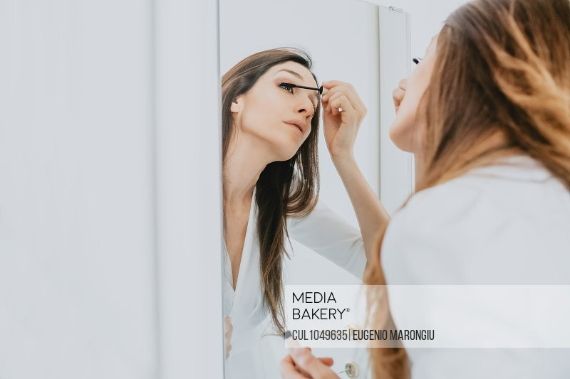Woman with brown hair standing in front of mirror, applying mascara.