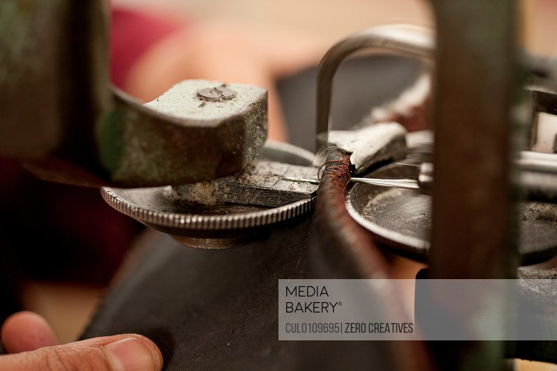 Close up of person using machine to work leather