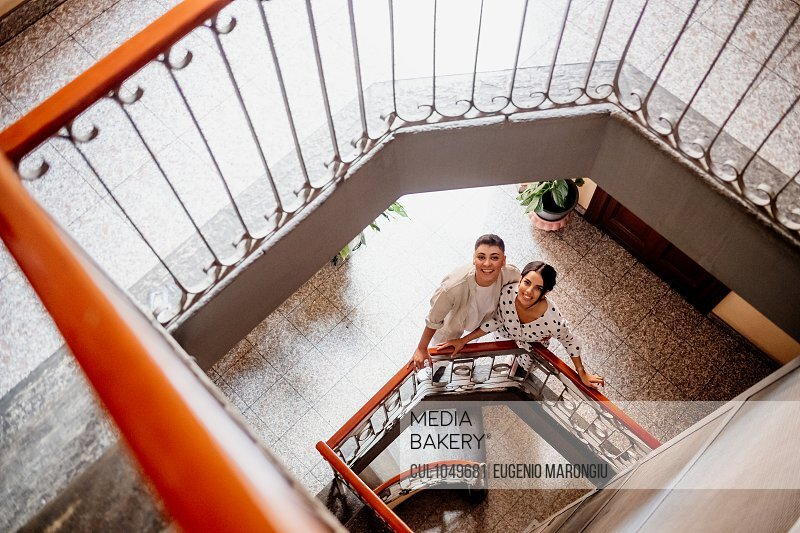High angle view of young lesbian couple standing at bottom of stairwell, looking at camera.