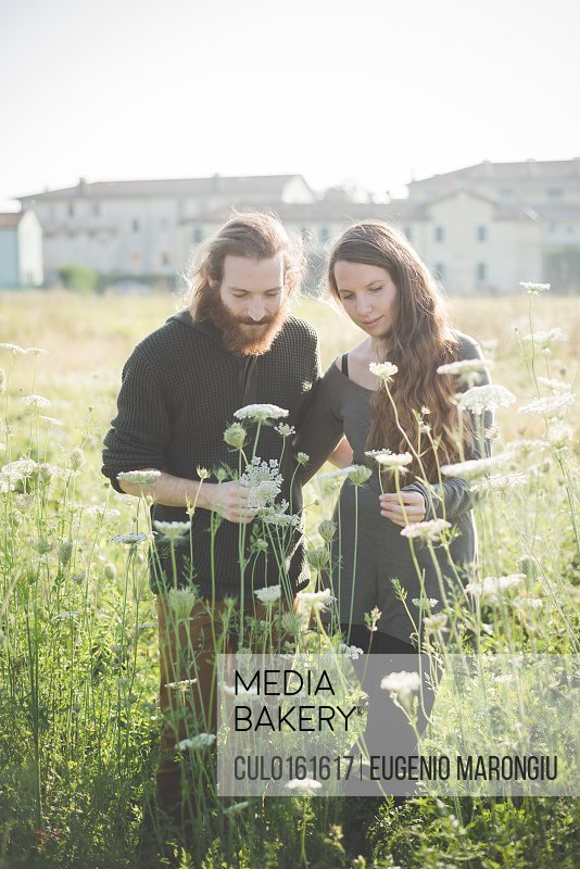Young couple picking wild flowers in field