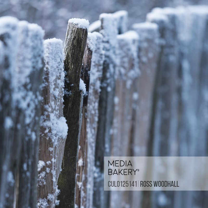 Snow covered wooden barrier