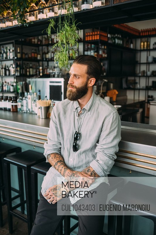 Portrait of bearded young man with brown hair, with tattoos on arms, wearing grey shirt, sitting at a bar counter.
