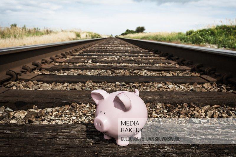 Piggy bank on railroad tracks