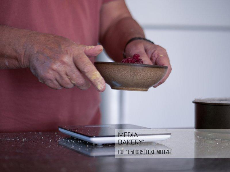 Man weighing ingredients for cake