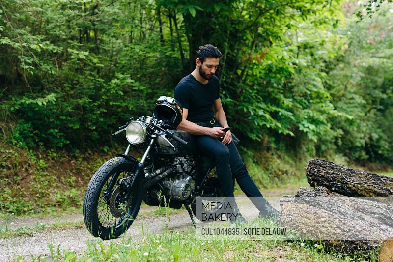 Young male motorcyclist on vintage motorcycle on rural roadside looking at smartphone, Florence, Tuscany, Italy