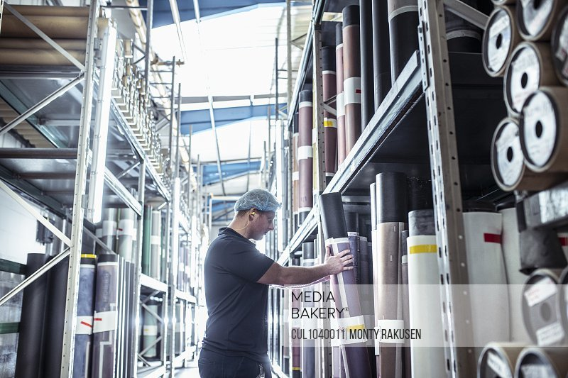 Worker selecting print rolls in print factory