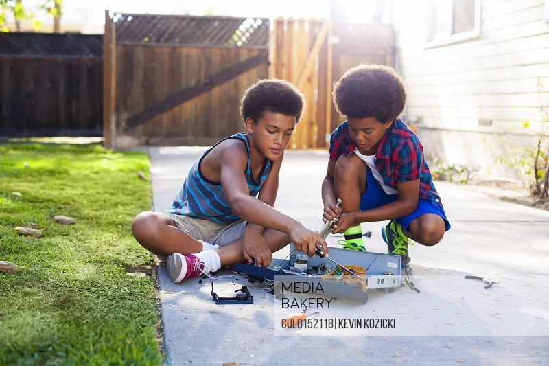 Two brothers dismantling electronic equipment in garden