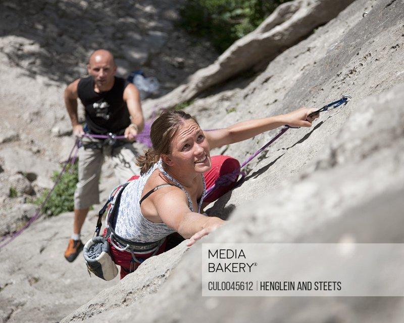 Rock climber climbing rock face