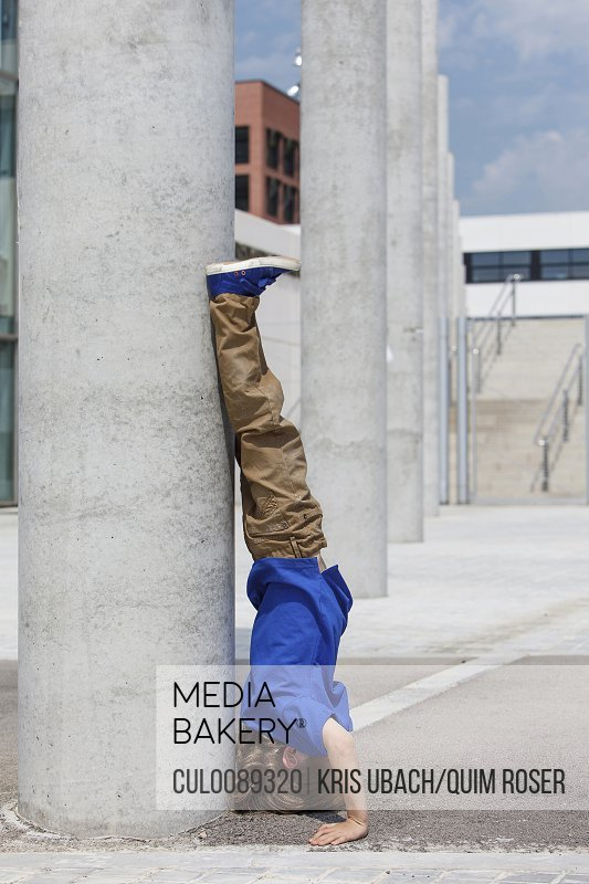 Boy doing headstand by column