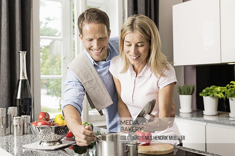 Mid adult couple preparing food
