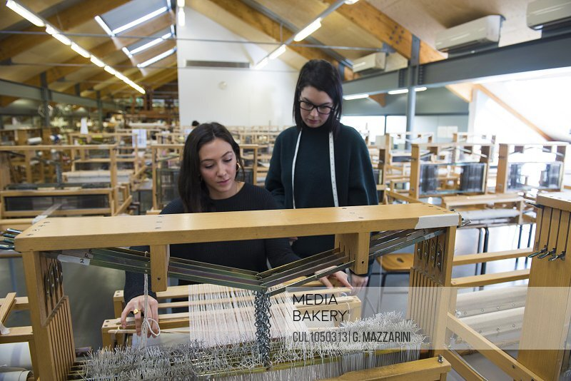 Students weaving with loom in textile workshop