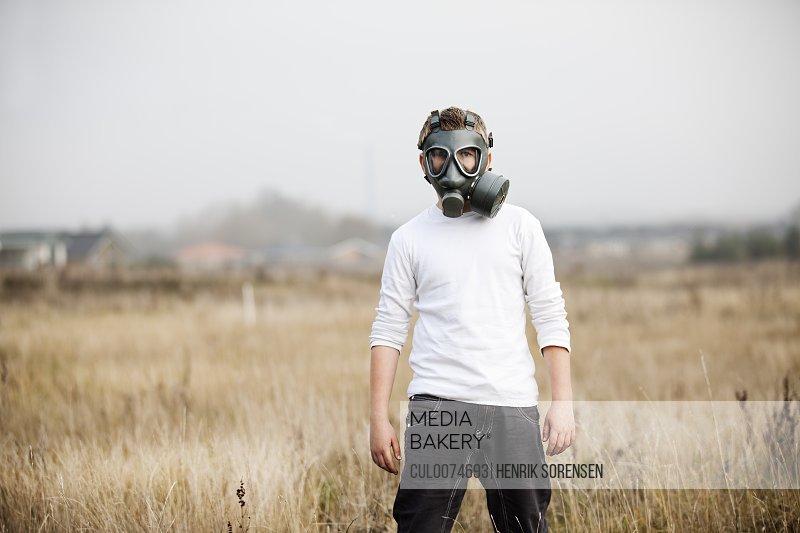 Boy wearing gas mask in wheatfield