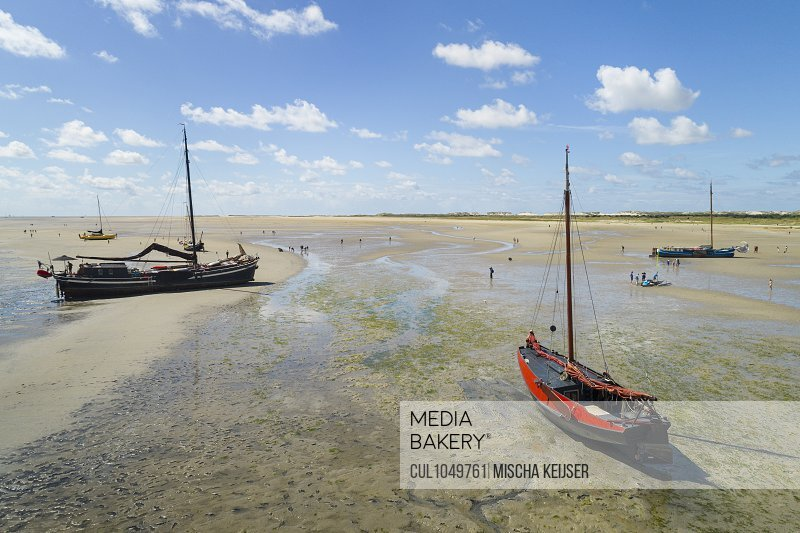 Flatbottom sailing ships beached on the Noordsvaarder nature reserve on the island of West-Terschelling, Friesland, Netherlands