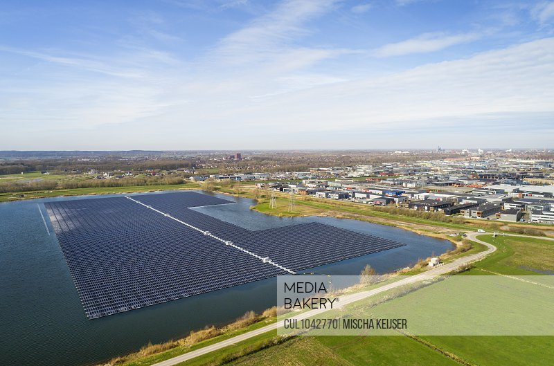 Aerial view of solar panels set on a lake in the countryside near an Industrial area.