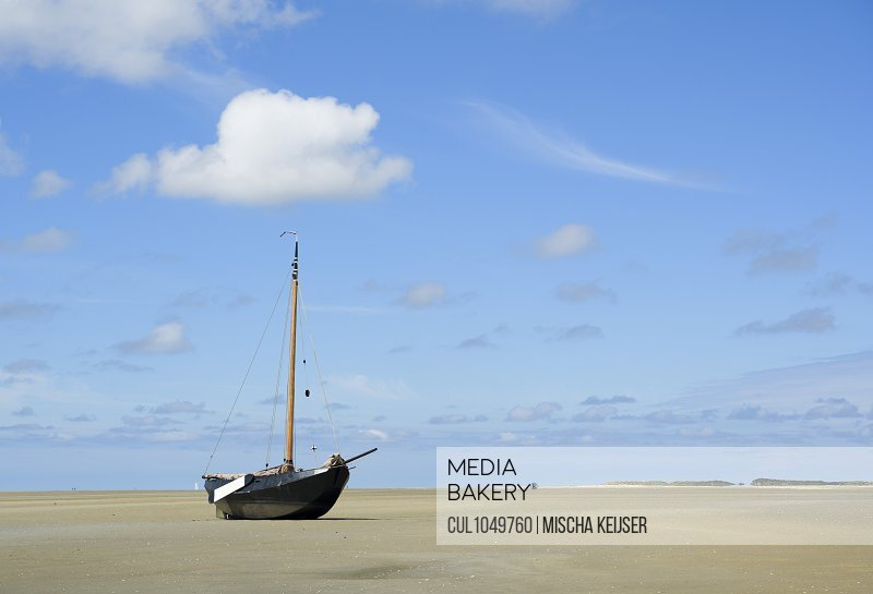 A Flatbottom sailing ship is beached on the Noordsvaarder nature reserve on the island of West-Terschelling, Friesland, Netherlands