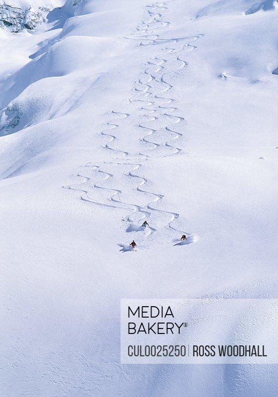 Three skiers skiing down a powder field