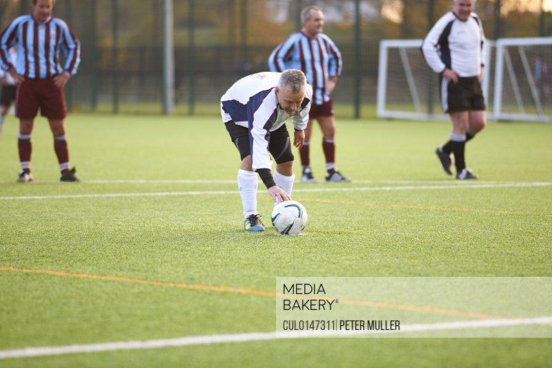 Football player positioning ball